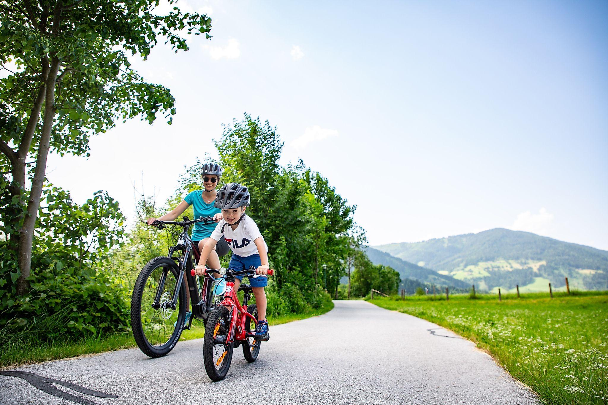 <p>Den Ennsradweg entlang radeln - Mama mit Kind genießt das Radeln abseits des Straßenverkehrs</p>